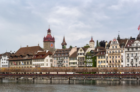 The Kapellbrucke (Chapel Bridge) is a covered wooden footbridge spanning diagonally across the Reuss River in the city of Lucerne, Switzerland photo
