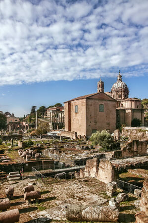 The Roman Forum is a rectangular forum (plaza) surrounded by the ruins of several important ancient government buildings at the center of the city of Rome. Curia and Santi Luca e Martina church photo