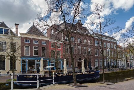 delft: View of Delft canal with historic houses and boat, Netherlands Stock Photo