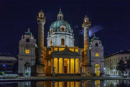 Karlskirche  (St. Charles Church) has garnered fame due to its dome and its two flanking columns of bas-reliefs, Vienna, Austria. Evening Stock Photo