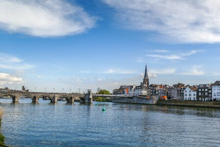 View of embankment of Meuse river with bridge in Maastricht, Netherlands