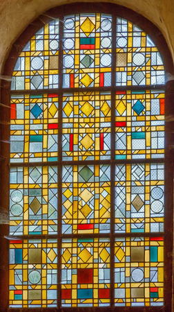 The Romanesque church (XIIth century) in Saint-Leon-sur-Vezere, Dordogne, France. Stained-glass window Banque d'images - 115764761