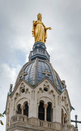 Bell tower of Basilica of Notre-Dame de Fourviere with a gilded statue of the Virgin Mary, Lyon, France