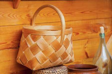 wicker work: basket of birch bark on a wooden wall Stock Photo