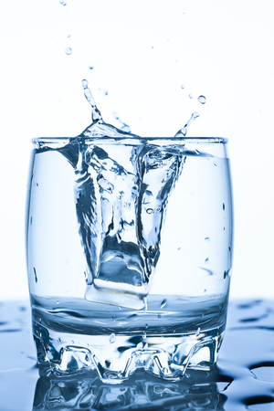 water splash in a glass with a piece of ice on a white background, a splash of water with spray droplets