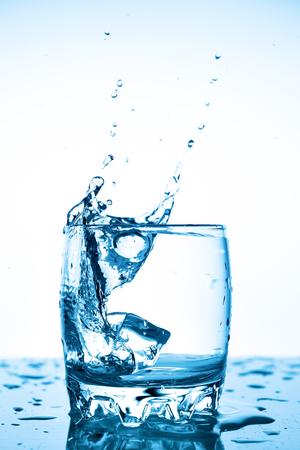 Wasserspritzer in einem Glas mit einem Stück Eis auf weißem Hintergrund, ein Stück Eis fällt ins Glas Tasse Wasser, Wasserspritzer fliegen in alle Richtungen