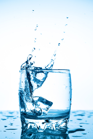 water splash in a glass with a piece of ice on a white background, a piece of ice falling into glass Cup of water, splashes of water flying in all directions