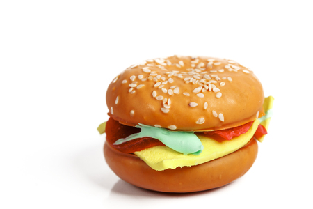 a cake resembling a hamburger isolated on white background closeup Imagens