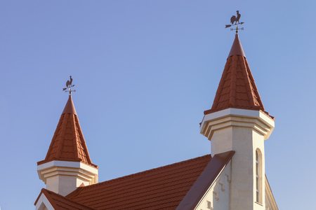 two towers with weathervanes on the background of blue sky