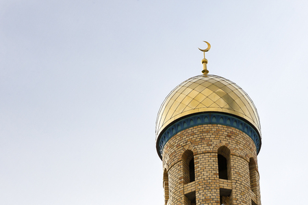 The Golden Crescent of the waxing moon,symbol of Islam, the Muslim religion, at the top of the temple, a minaret against the blue sky. Stock Photo