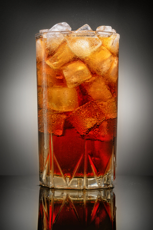 glass of Cola with ice on grey background with reflection
