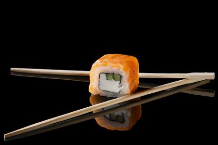 sushi rolls with chopsticks on black background Stock Photo