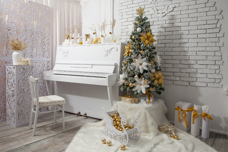 Room with a white piano and a Christmas tree
