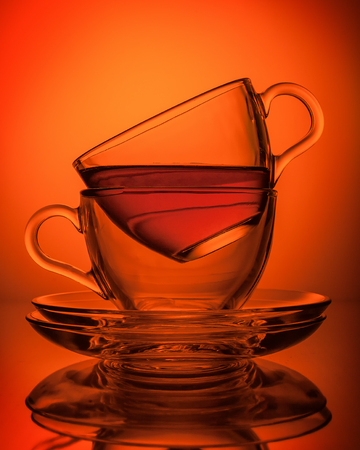 Two cups of tea made of transparent glass, facing each other with a saucer orange background