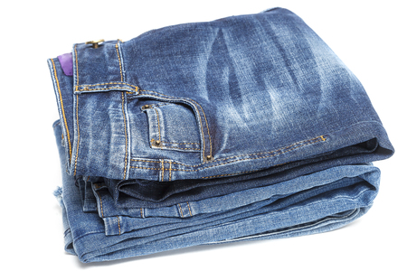 denim pants folded in a pile on a white background, blue jeans