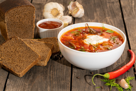 Russian borsch on a wooden table with black bread and seasonings Imagens