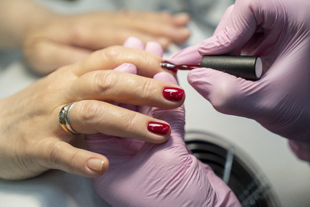 do manicure, nail red lacquer close-up