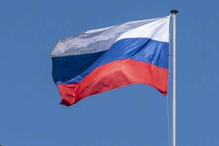 flag of Russia, the Russian Federation, the tricolor against the blue sky develops in the wind close-up Imagens