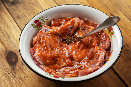 raw meat marinated in sauce for barbecue in a metal Cup on a wooden table