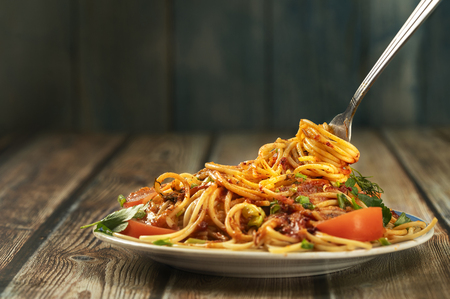 plate of pasta seasoned with herbs, tomatoes and sauce on a wooden table close-up, fork with long pasta and sauce, share menu restaurant and cafe
