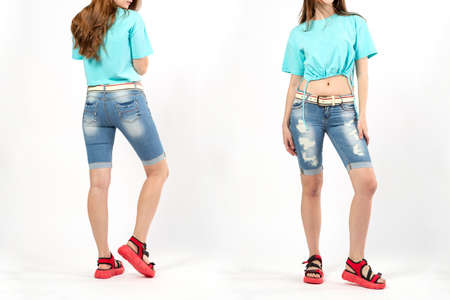 women's denim short shorts with a belt, a girl in denim shorts on a white background in red summer sports shoes