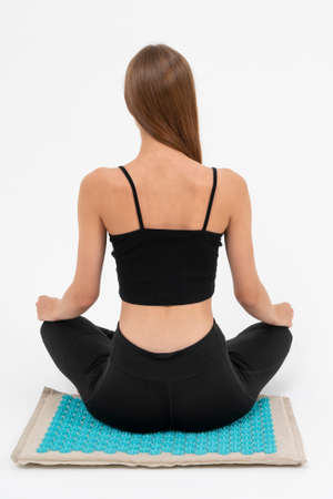 the girl meditates on the massage Mat, she receives acupuncture treatments on a white background Imagens