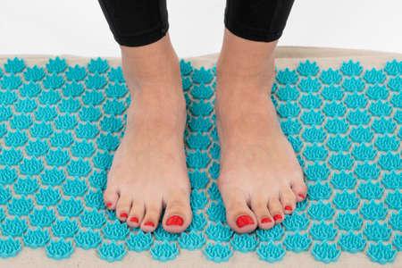 women's feet on a massage Mat, close-up, girl standing on applicators doing foot massage on a massage Mat