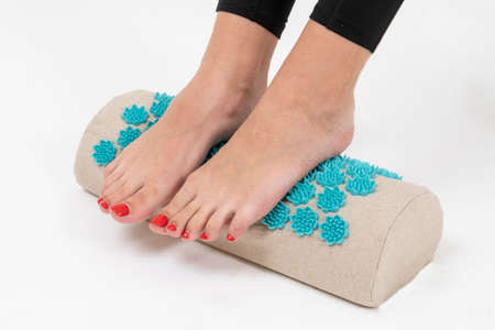 women's feet on a massage Mat, close-up, girl standing on applicators doing foot massage on a massage Mat