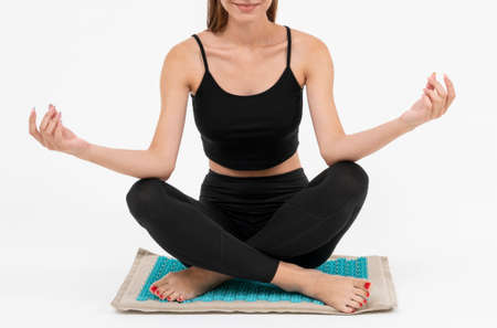 the girl meditates on the massage Mat, she receives acupuncture treatments on a white background
