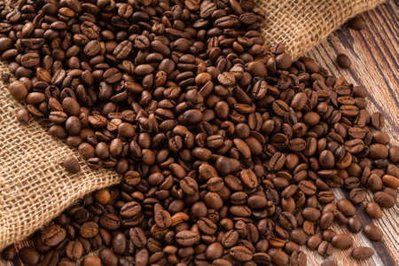 coffee background, coffee beans on burlap and wooden table