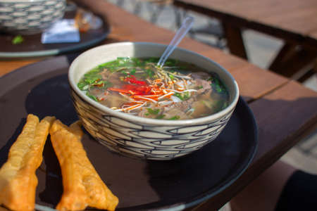 Asian food in a plate, rice noodles soup, street food in cafe