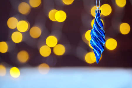 The Christmas Christmas-tree decoration, icicle hangs against the background of yellow a bokeh