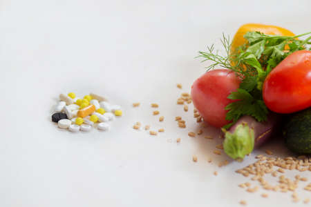The small group of tablets lies nearby with vegetables on a white background Stock Photo