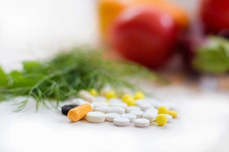 The heap of tablets, drugs lies against the background of fresh vegetables