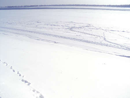 Snowy winter landscape on the banks of a frozen river. A lot of snow and snowdrifts. Footprints on ice. Zdjęcie Seryjne