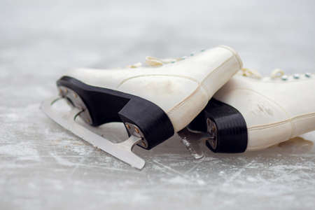 White ice skates for figure skating lie on an ice rink