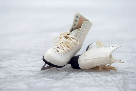 A pair of White Figure Skates lie on an open ice rink