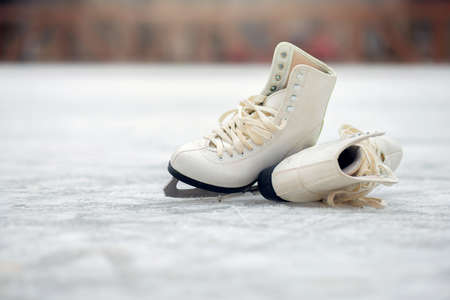 A pair of White figure skates lie on an open ice rink. Winter sport