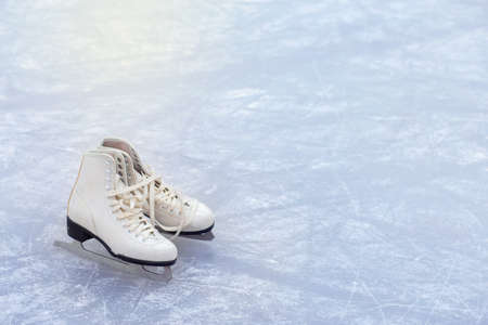 A pair of White figure skates are standing on an ice rink in the corner of the frame. Winter sport