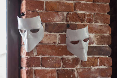 Two white terrible masks hang on a brick wall near a window Reklamní fotografie