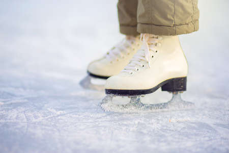 A child in figure skates stands on the ice, closeup skates. Ice skating in winter at the rink