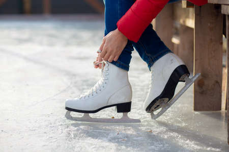 A girl is tying shoelaces on figured white skates on an ice rink