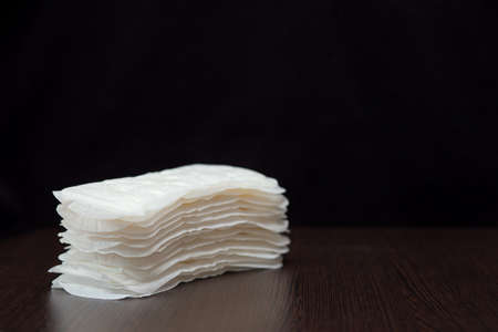 Women's white sanitary pads for every day are stacked on a black background Standard-Bild