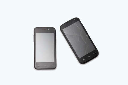 Two black phones lie on a white background. The broken smartphone. Cracks on the screen.