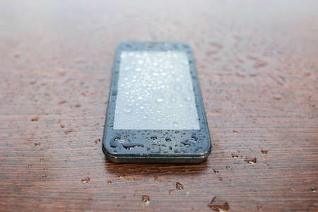 Black phone the smartphone lies on a wooden background, splashed by water drops.