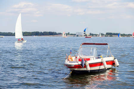 Red motor boat moored to the shore. In the background are many yachts with sails. Summer is in full swing