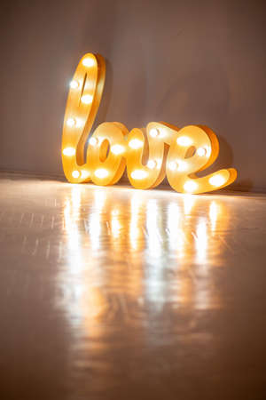 Luminous word LOVE made of wood and incandescent bulbs. St. Valentine's Day. Design option