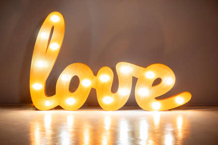 Luminous word LOVE made of wood and incandescent bulbs