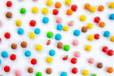 Scattered multi-colored small round candies. Pattern of chocolate dragees in multi-colored glaze on a white background 免版税图像