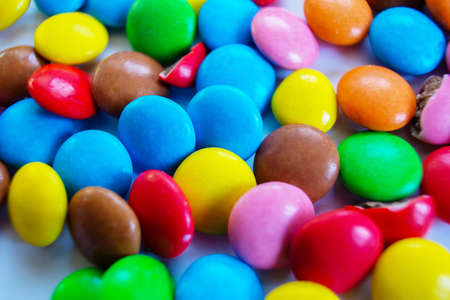 Many multi-colored small round candy pills are scattered on the table close-up